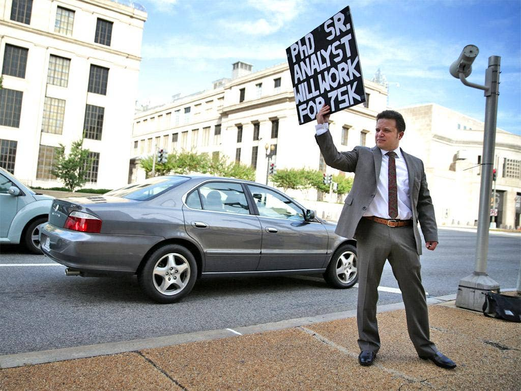 Matthew Giarmo of Alexandria, Virginia, holds up a sign seeking a job on a street corner in Washington, DC