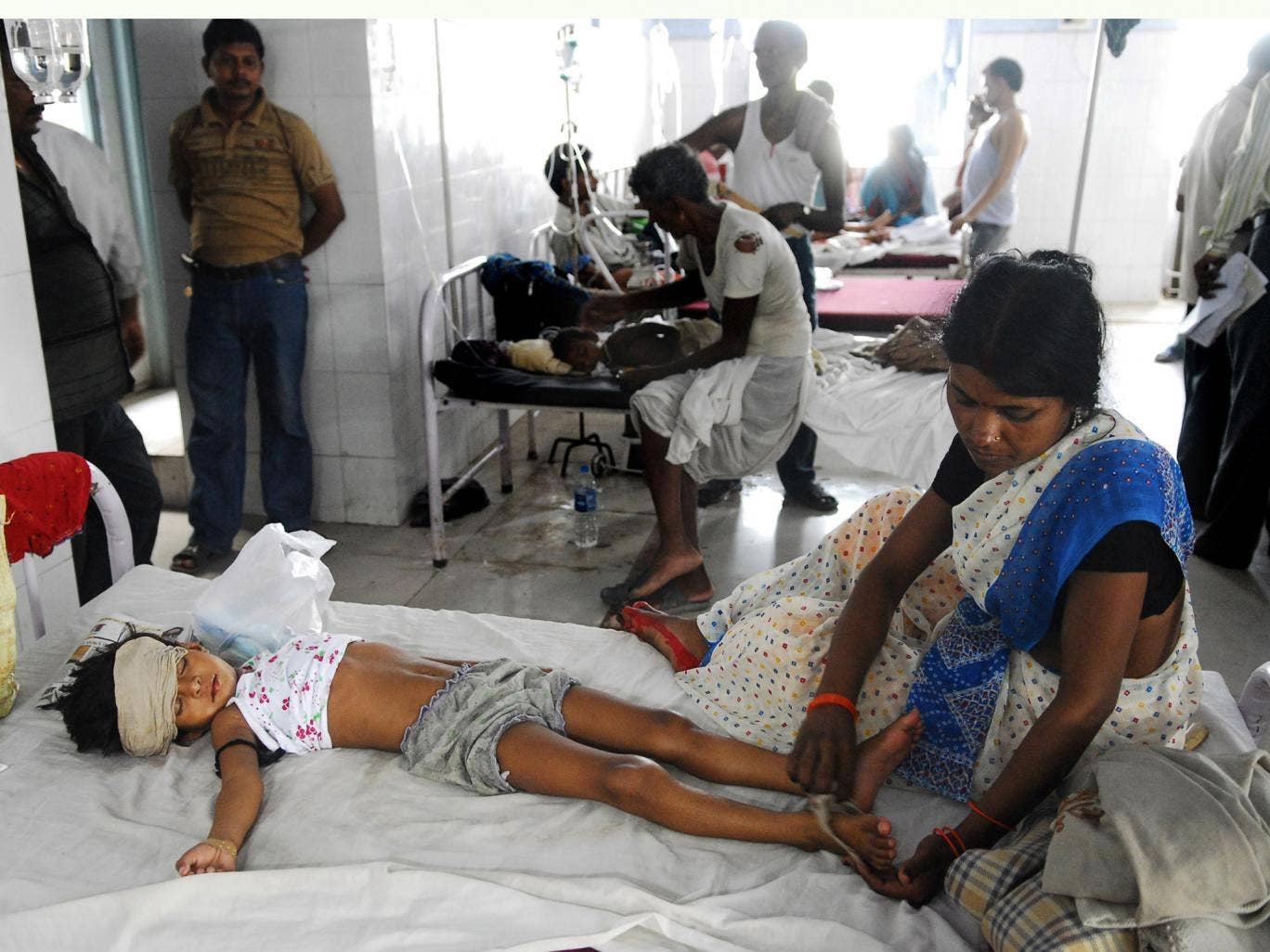 An Indian woman attends to a child lying in a bed in hospital. Health officials are battling to confront a new outbreak of encephalitis, a disease that has this year killed at least 350 children in one state alone