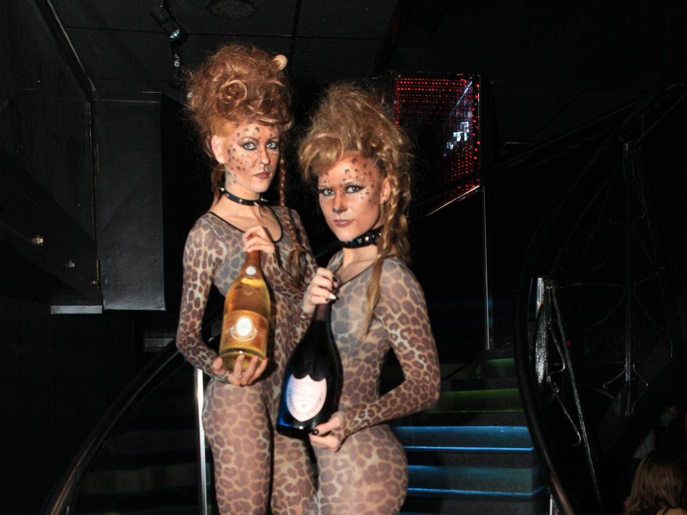 Waitresses at Kitsch nightclub hold bottles of champagne