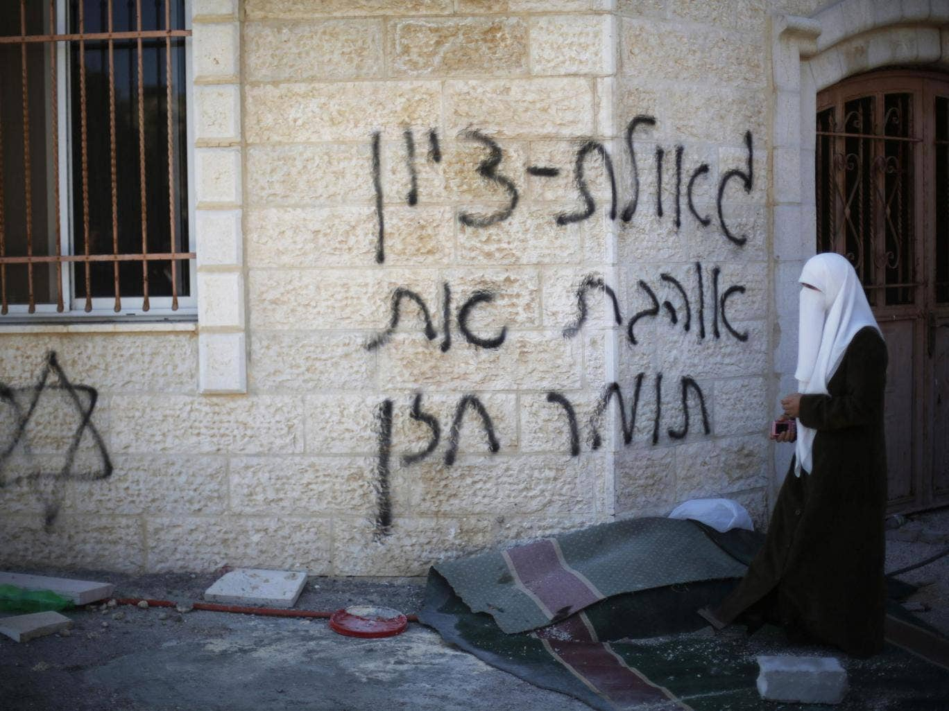 A Palestinian woman walks near the vandalised wall of a mosque in the West Bank village of Burka
