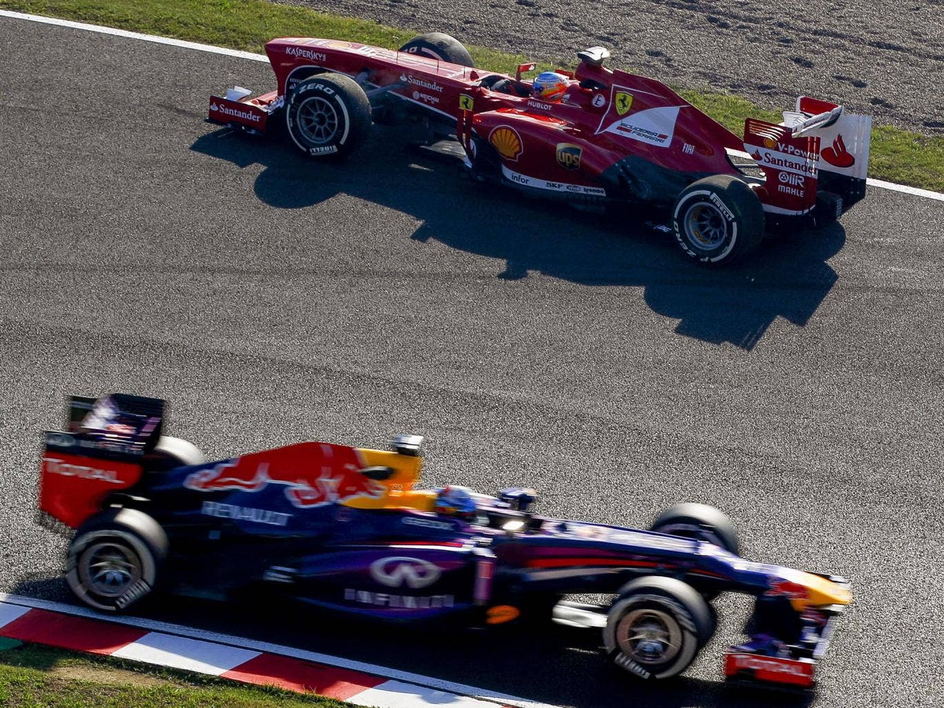 Sebastian Vettel (bottom) drives past Fernando Alonso, who is facing the wrong way after spinning during practice