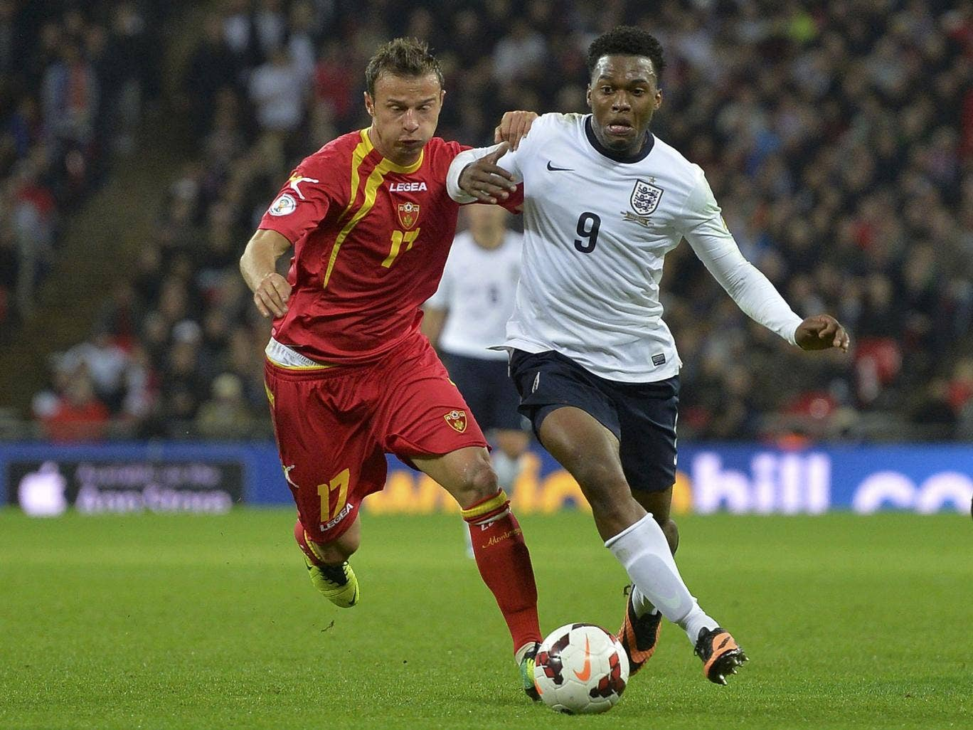 Daniel Sturridge, left, takes on Elsad Zverotic, right, of Montenegro, at Wembley