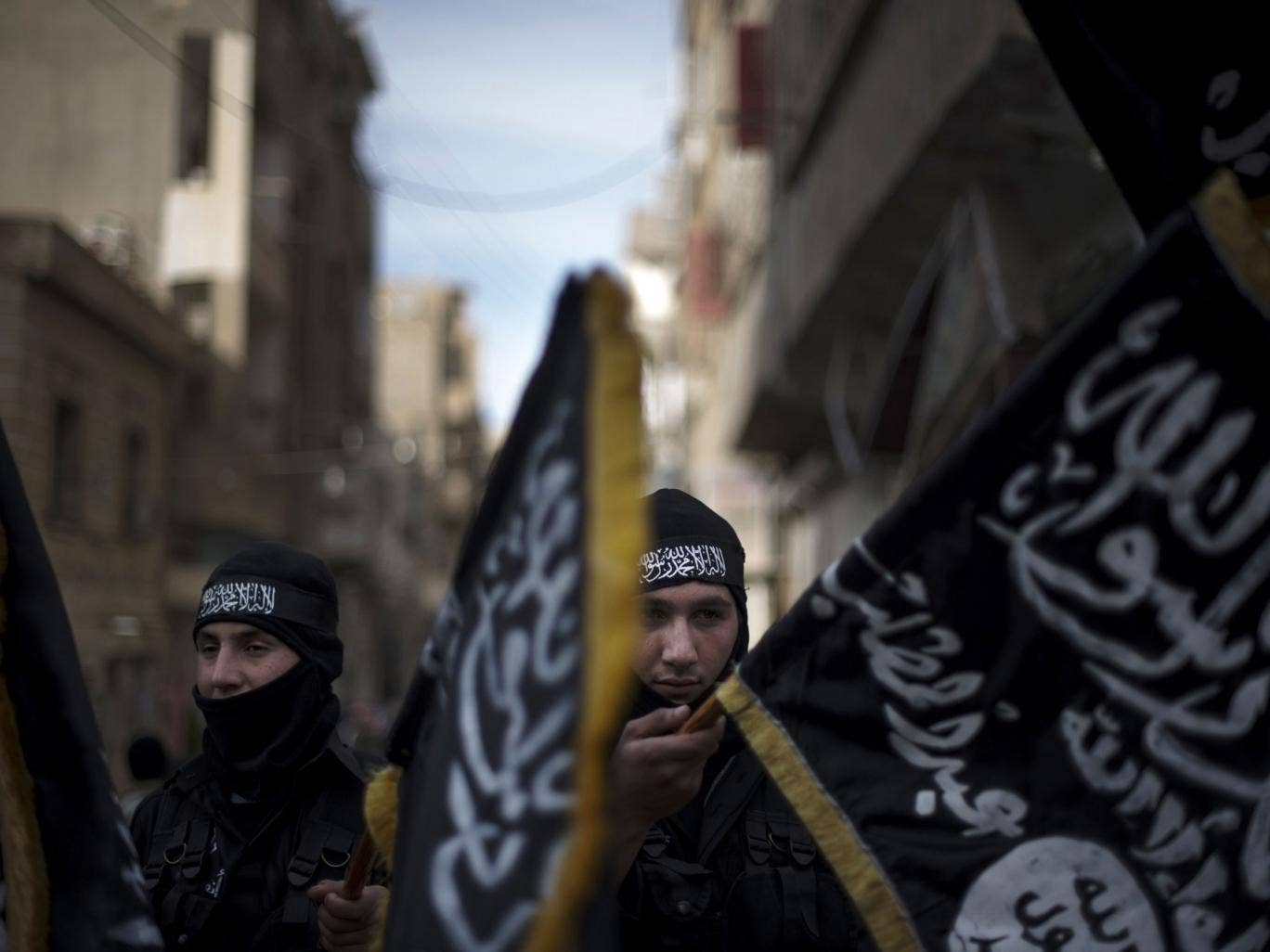 Members of the Islamist Liwa (brigade) Hamzah hold flags of Jebhat al-Nusra at a rally in Deir Ezzor earlier this year
