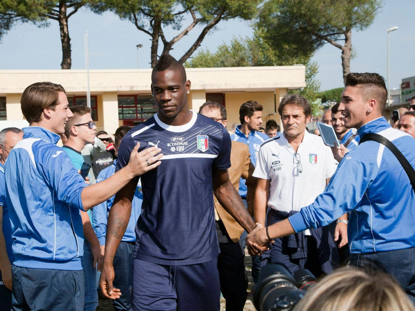 Mario Balotelli is greeted by Italian supporters ahead of their training session in Quarto