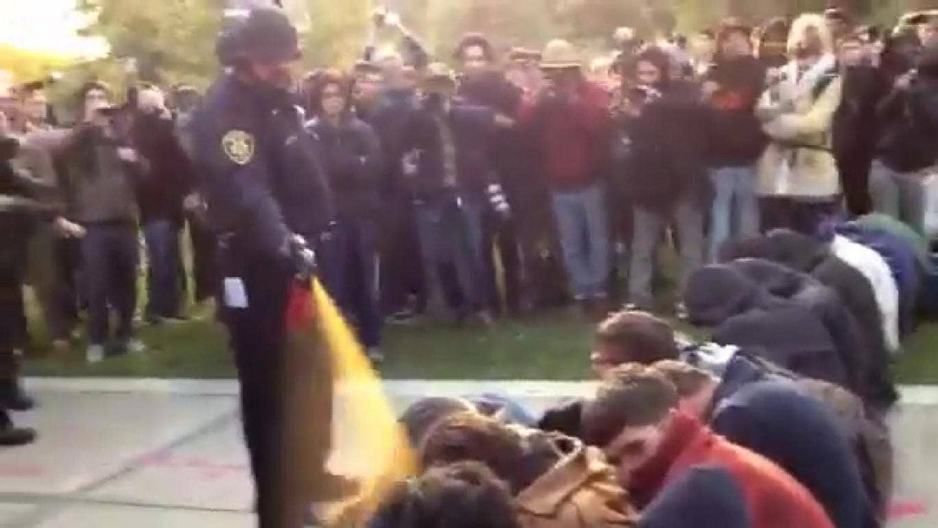 In this image made from the video, a police officer uses pepper spray as he walks down a line of Occupy demonstrators sitting on the ground at the University of California, Davis