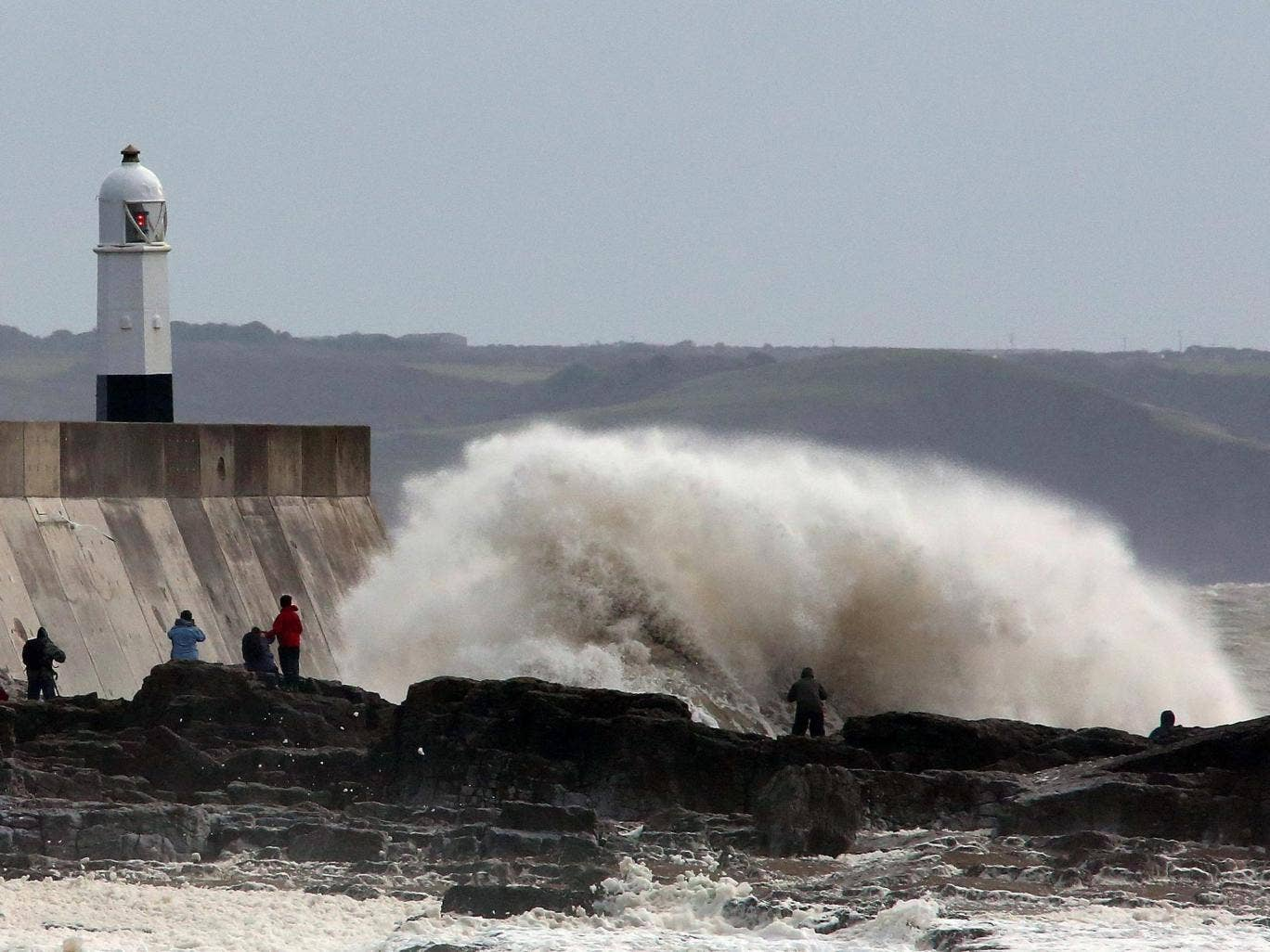 People stand on the sea wall at Porthcawl, south Wales, as heavy seas pound the harbour