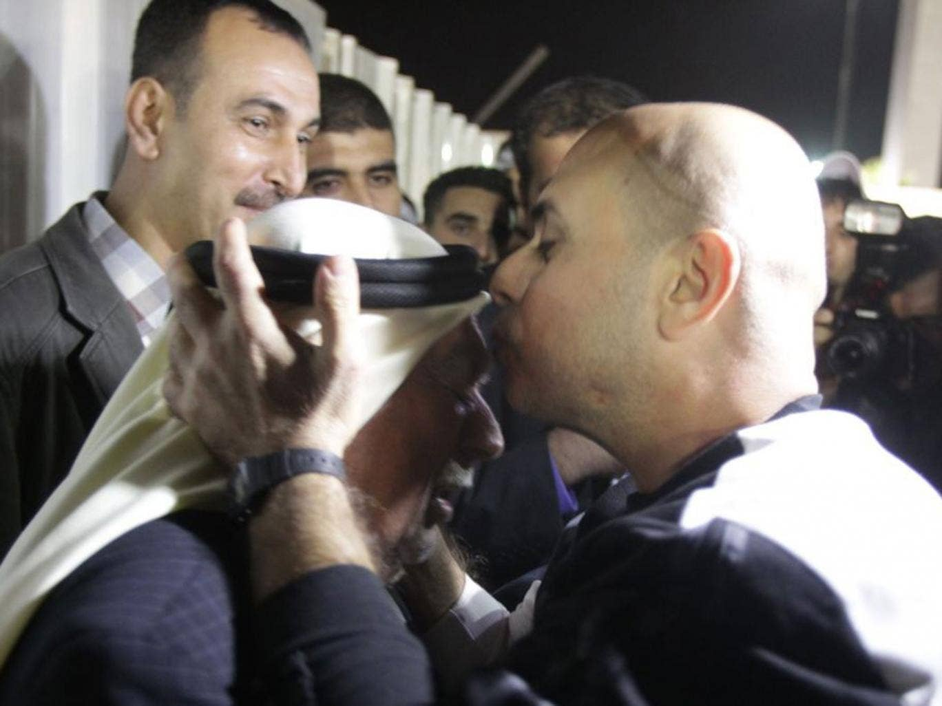 A released Palestinian prisoner kisses his father's head upon his arrival in the West Bank City of Ramallah, 30 October 2013