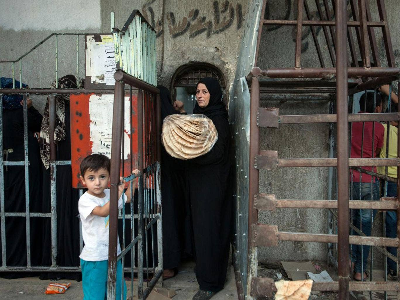 A Syrian woman carries bread from a bakery run by the Islamic rebel group 'Ahrar Al-Sham' amid claims the Assad regime has stopped aid getting through leaving residents to fend for themselves or starve