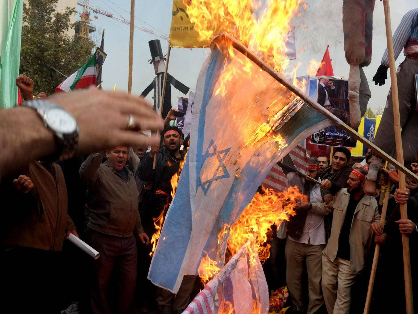 People burn Israel and U.S. flags a demonstration to mark the 34th anniversary of the 1979 US embassy takeover