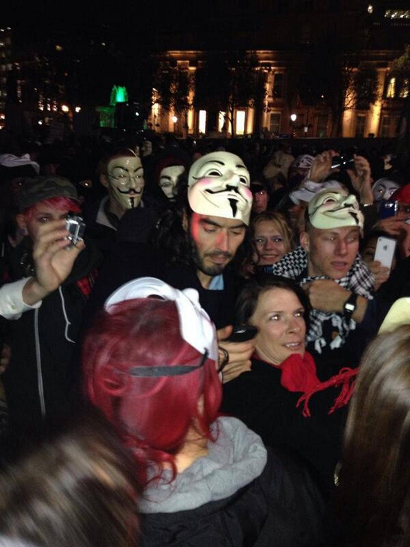 Russell Brand removes his Guy Fawkes mask while on a protest in London organised by Hacktivist group Anonymous