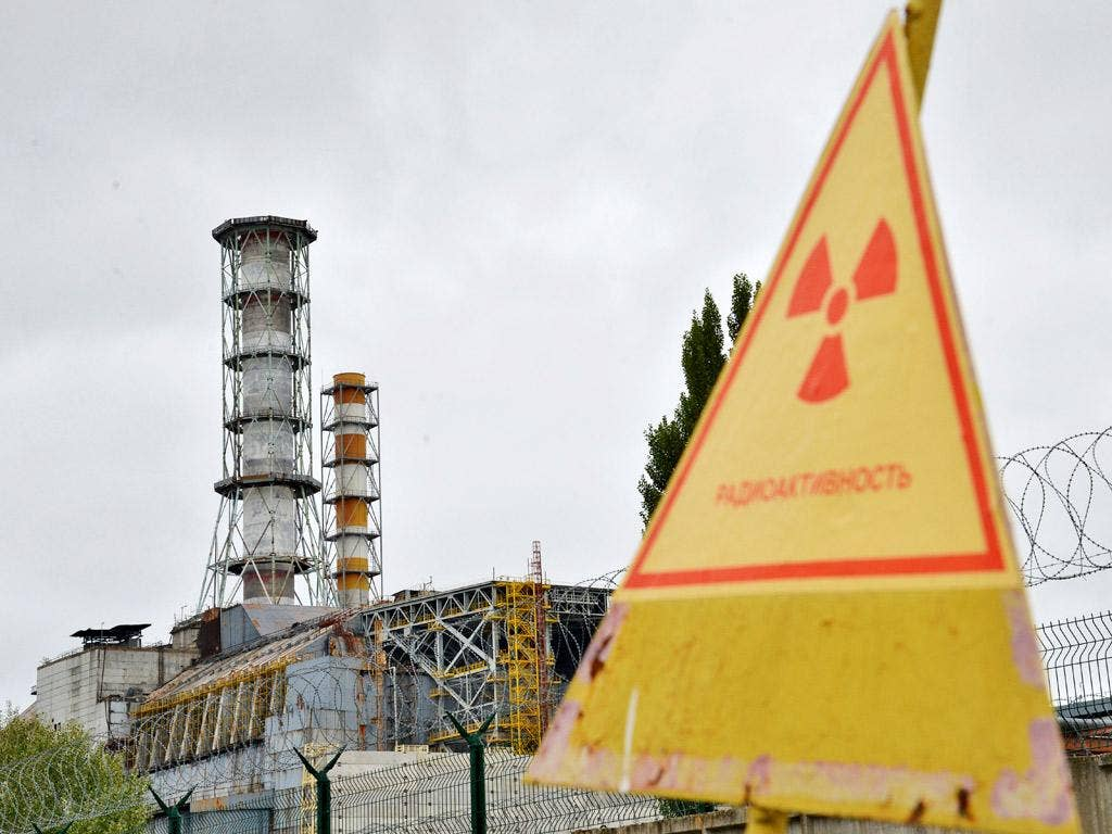 A view of a radioactive sign near a shelter and containment area built over the destroyed 4th block of Chernobyl's old nuclear power plant