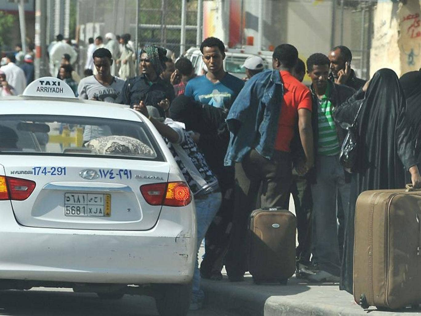 Foreign workers wait for a taxi to leave the Manfuhah neighbourhood of Riyadh on 10 November, after two people have been killed in clashes between Saudi and other foreign residents the previous day