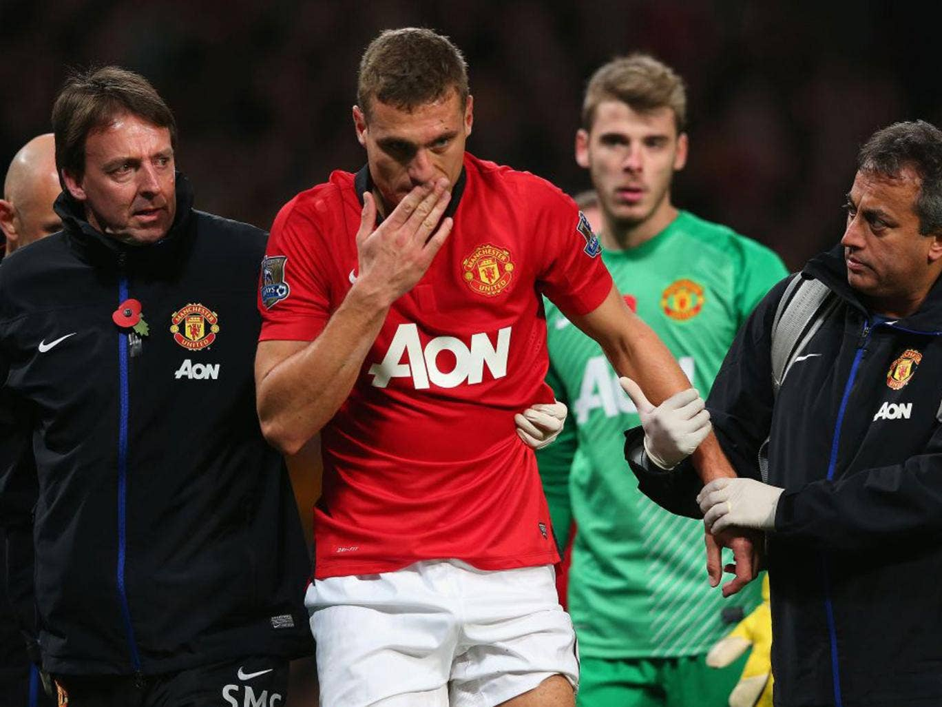 Nemanja Vidic of Manchester United is helped off the pitch