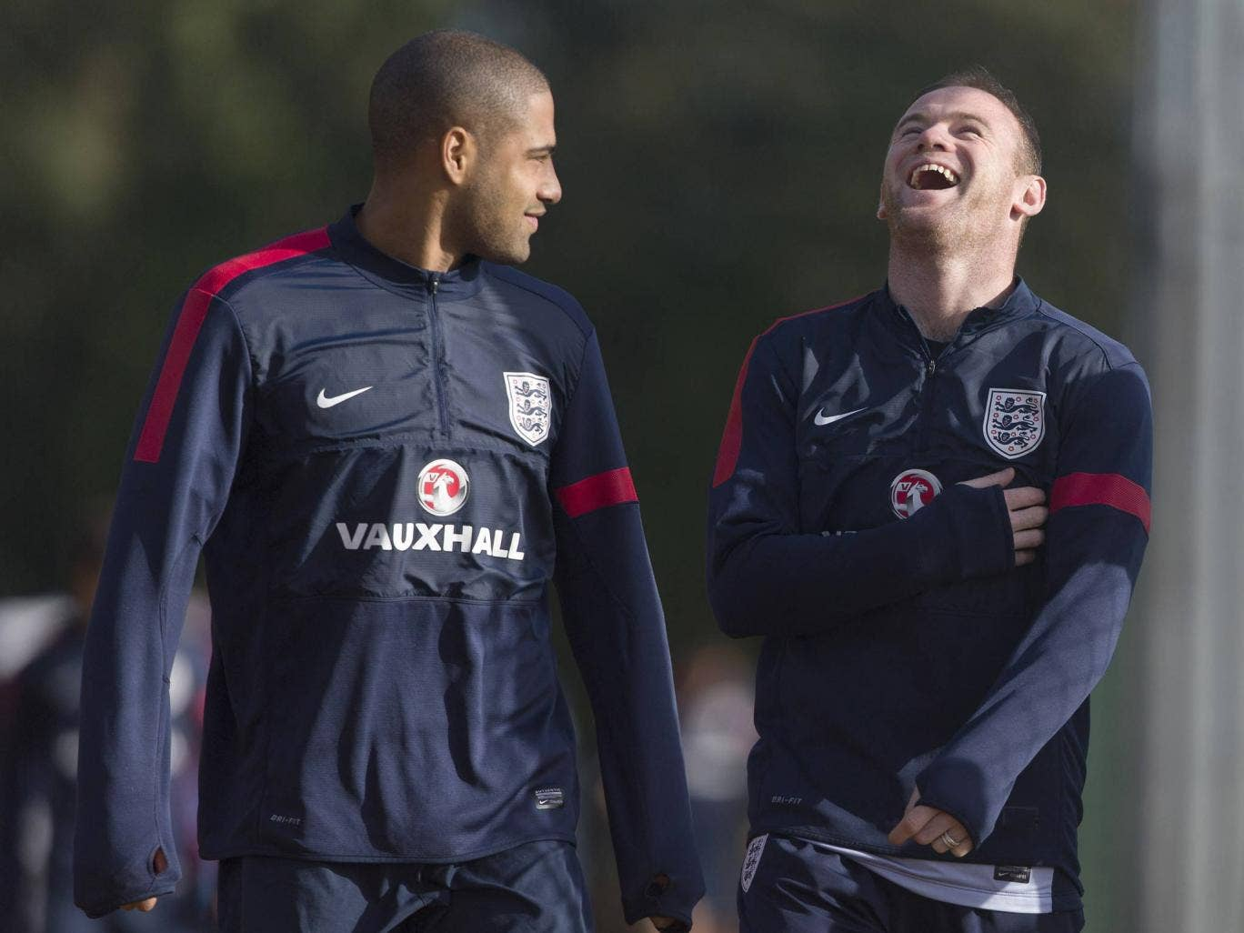 England footballers Glen Johnson (L) and Wayne Rooney (R) share a light moment as they arrive for a training session at Arsenal's training ground