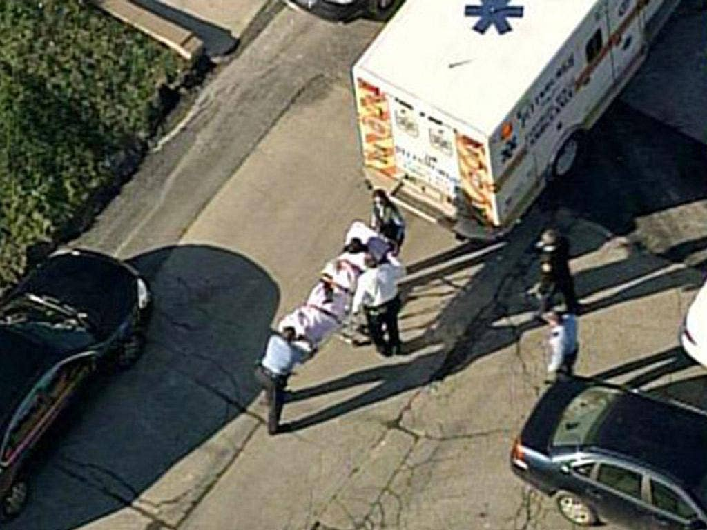 One of the victims is loaded into an ambulance near Brashear High School in Pittsburgh