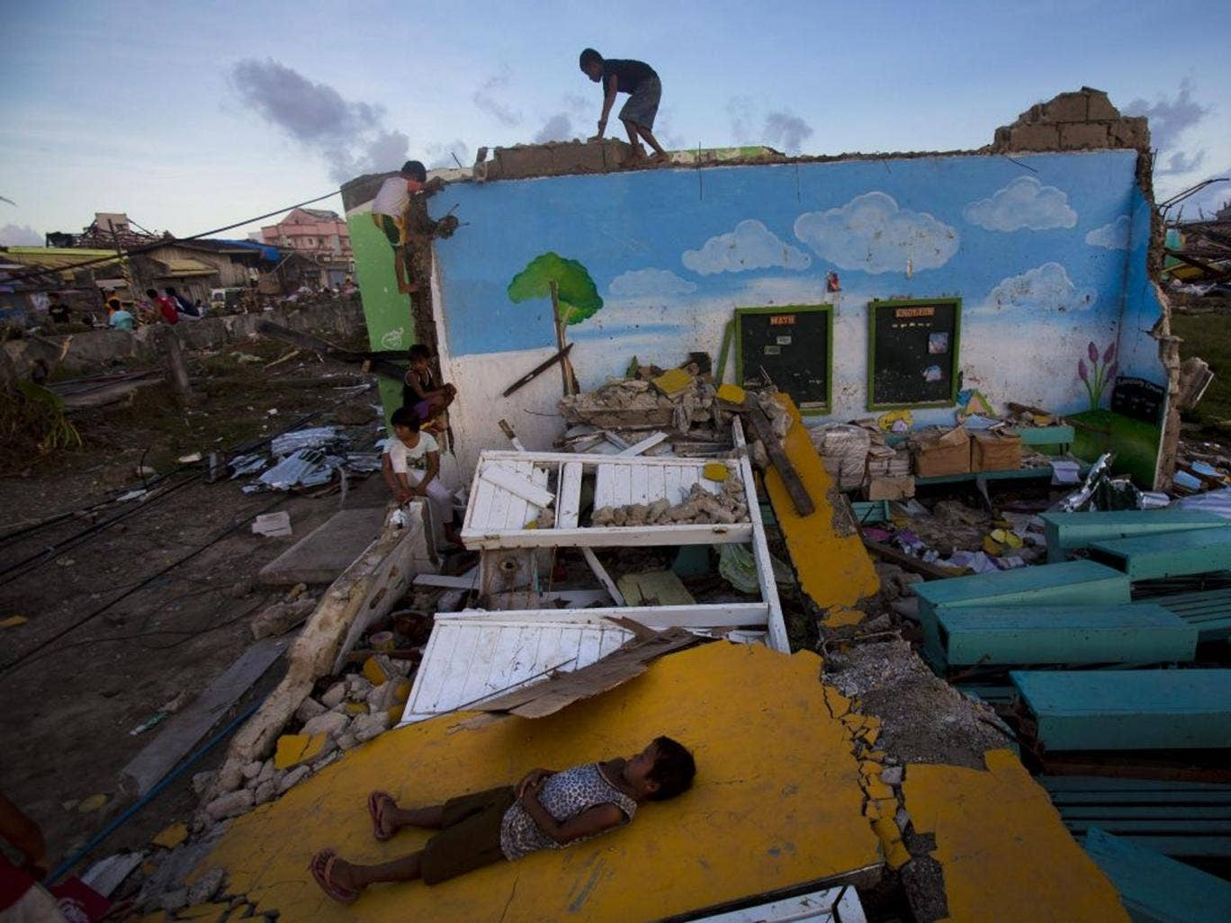 Children who survived Typhoon Haiyan play on top of the ruins of their destroyed primary school in Guiuan, Philippines