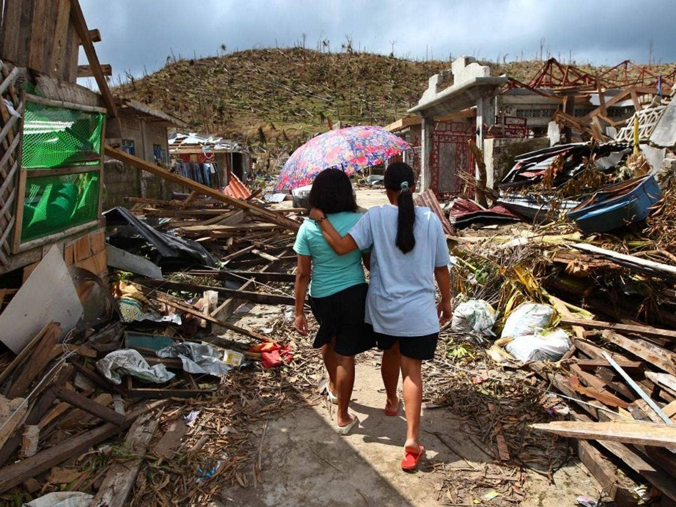 Typhoon Haiyan survivors walk amid ruins of buildings in Maraboth, Philippines