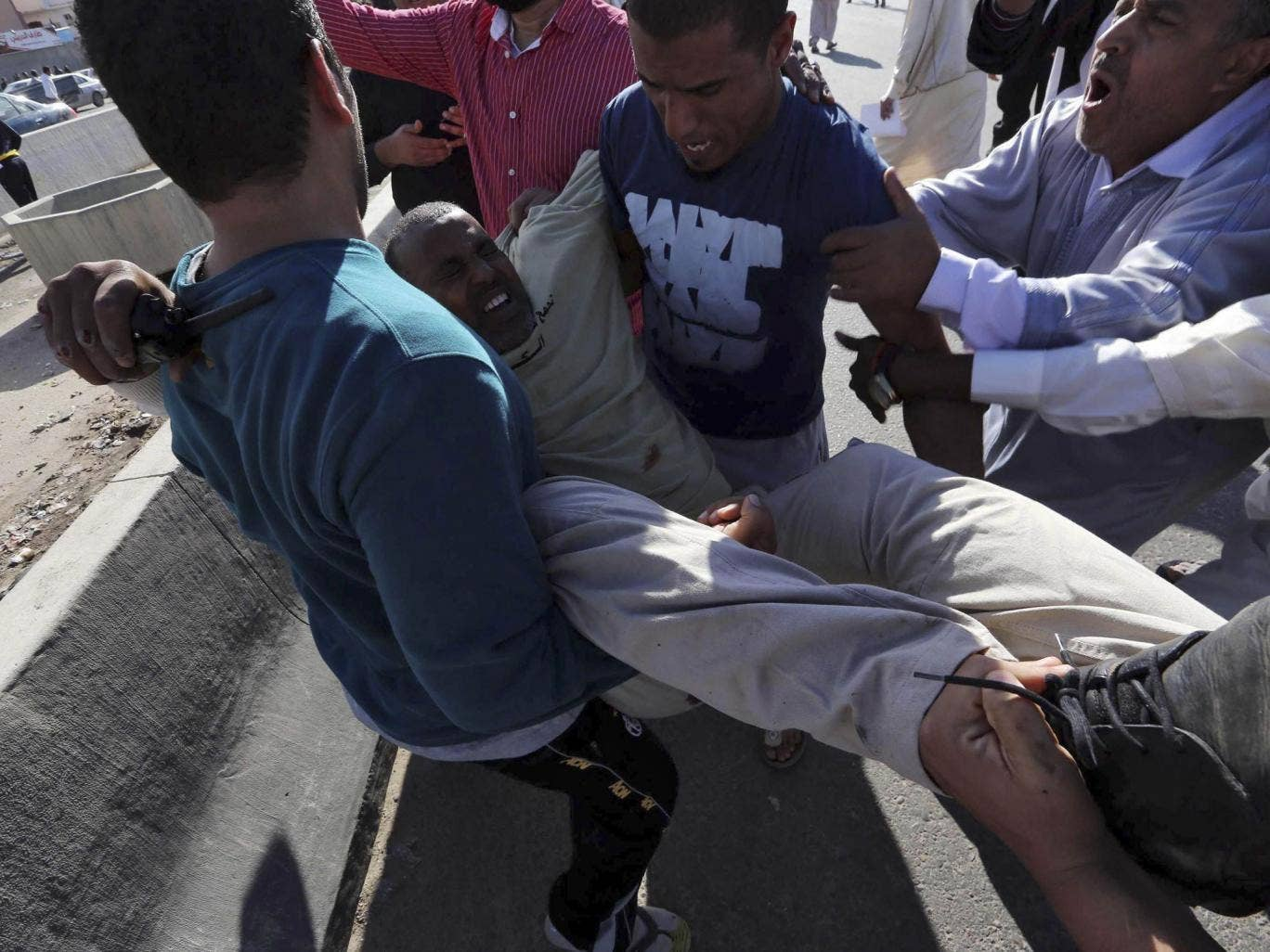 People carry an injured man after militiamen opened fire into hundreds of protesters