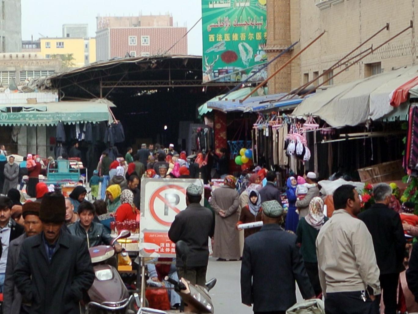 A crowd of mainly Uighur shop at a bazaar in China's Xinjiang region