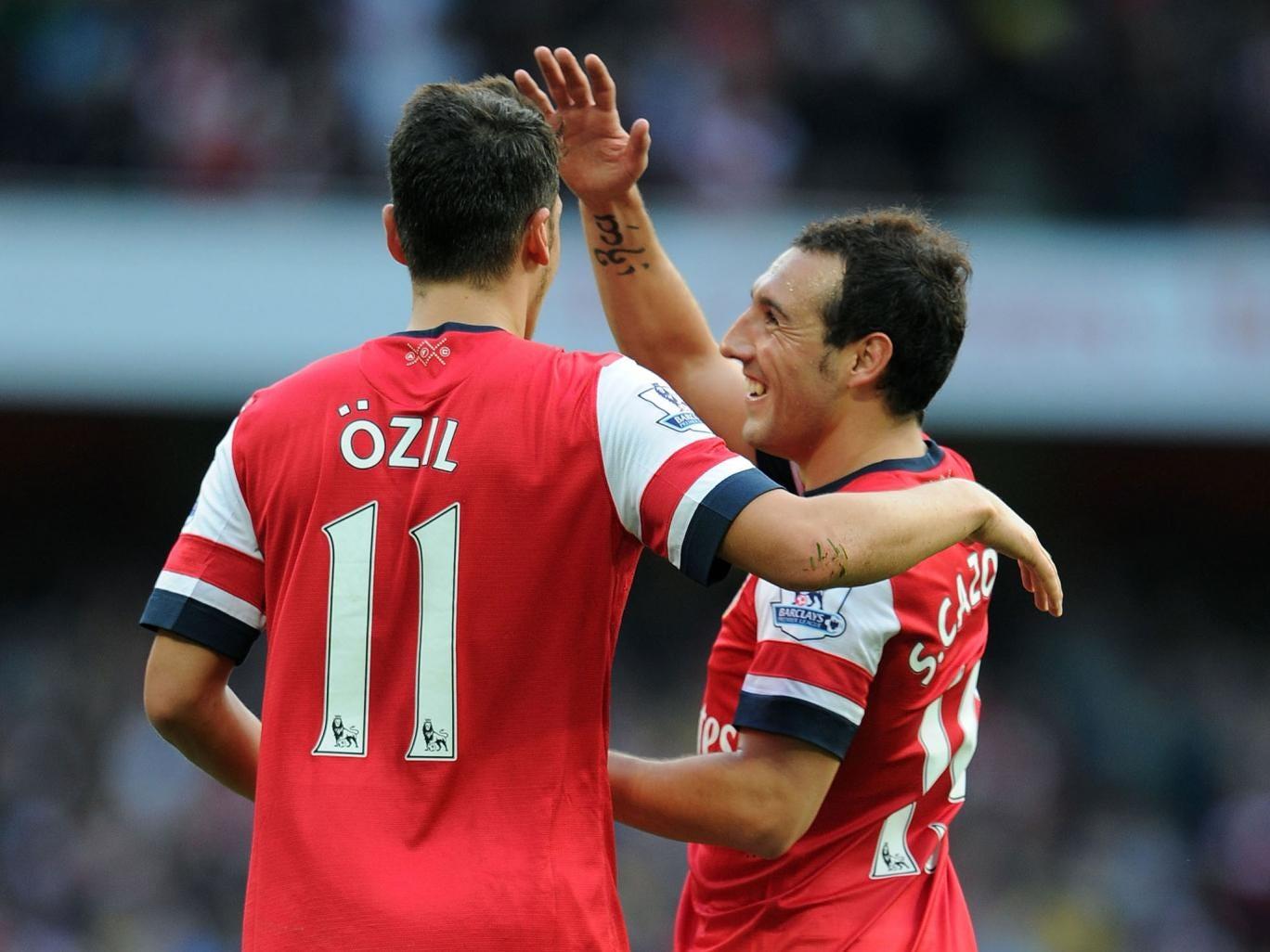 Mesut Ozil celebrates his second goal for Arsenal against Norwich City last month with Santi Cazorla