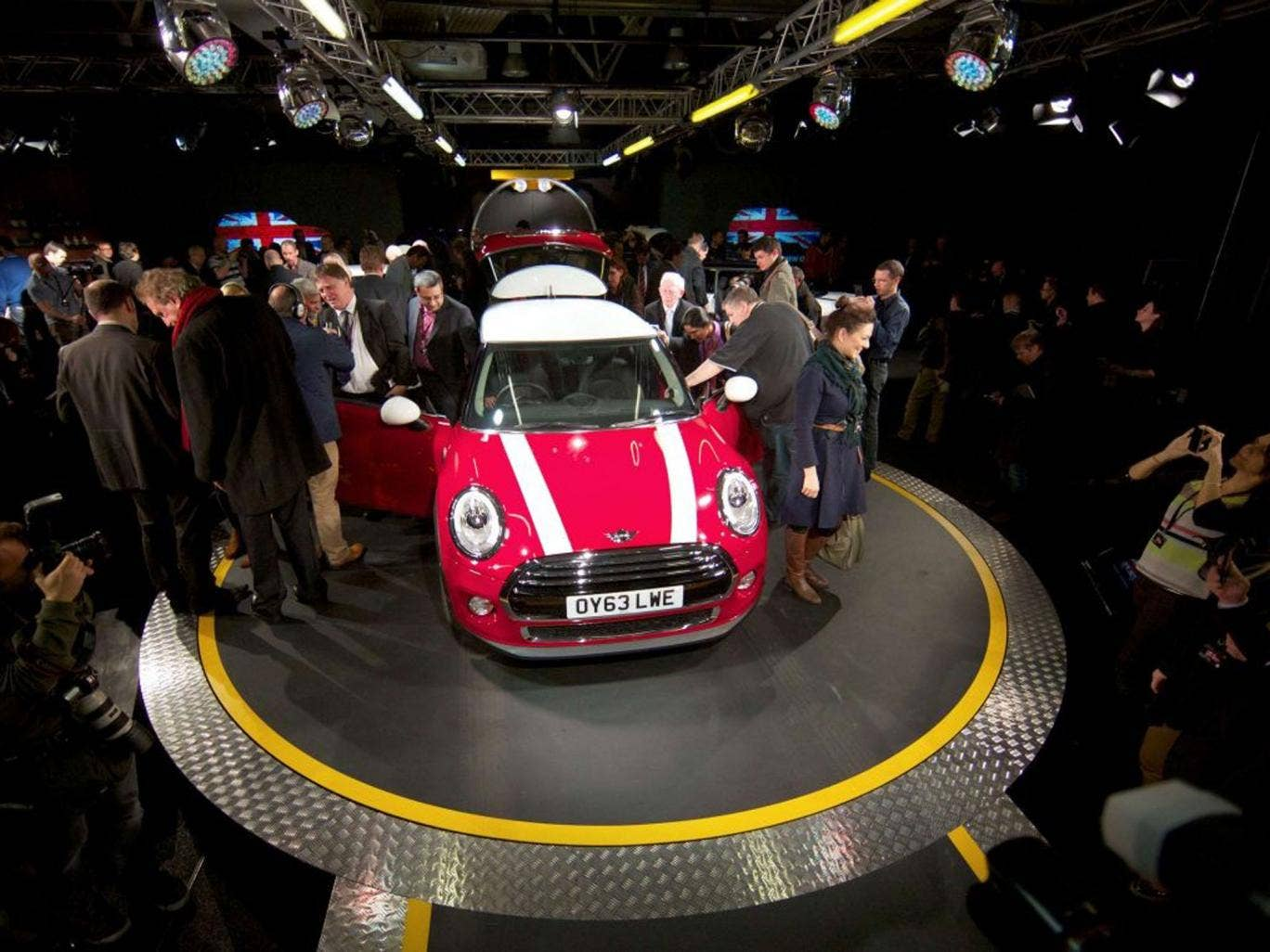 Journalists inspect the new Mini Cooper during its official unveiling at BMW's plant at Cowley in Oxford, England
