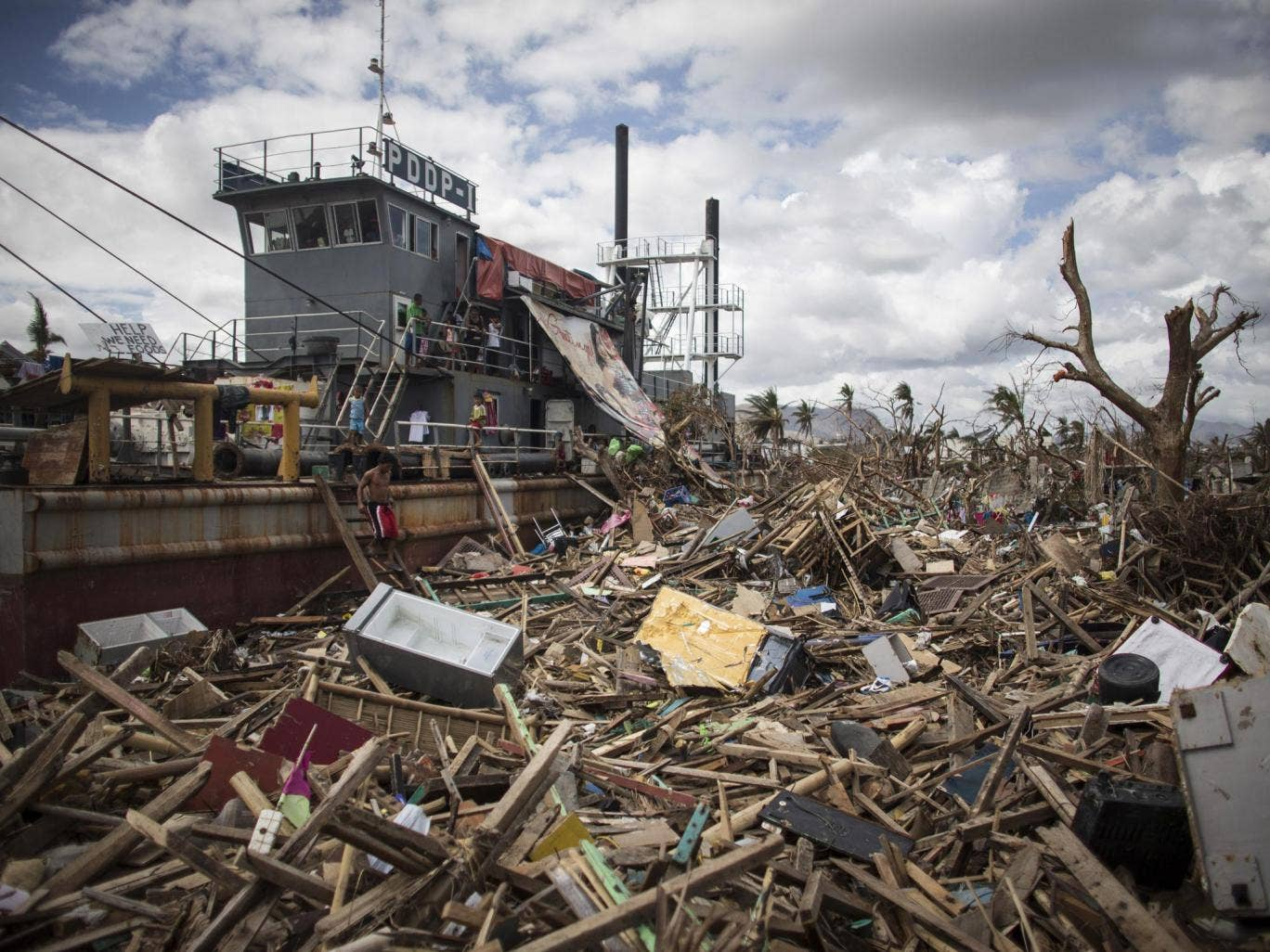19 November 2013: A man walks down steps from a tanker that was washed ashore in a particularly badly damaged part of Tacloban during Typhoon Haiyan in Leyte, Philippines