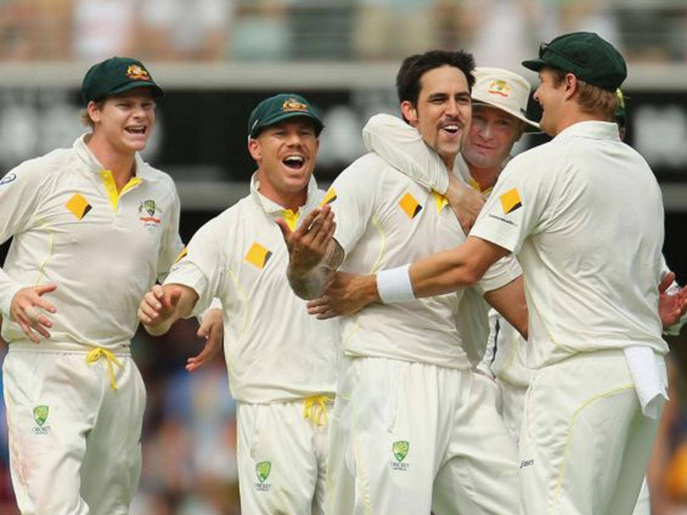Mitchell Johnson celebrates with his team-mates after taking his fourth wicket