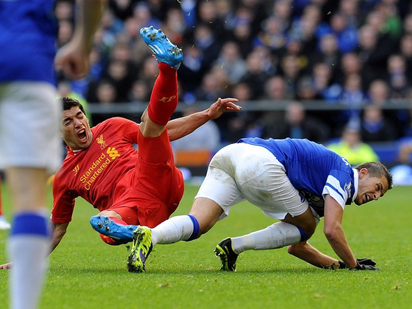 Kevin Mirallas of Everton tackles Luis Suarez of Liverpool