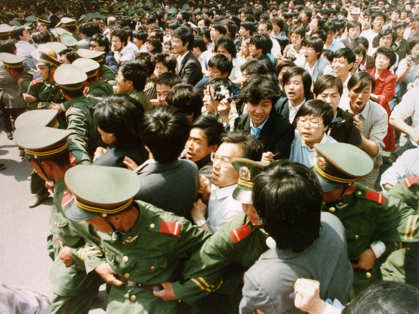 Crowds of jubilant students surge through a police cordon before pouring into Tiananmen Square on 4 June 1989.
