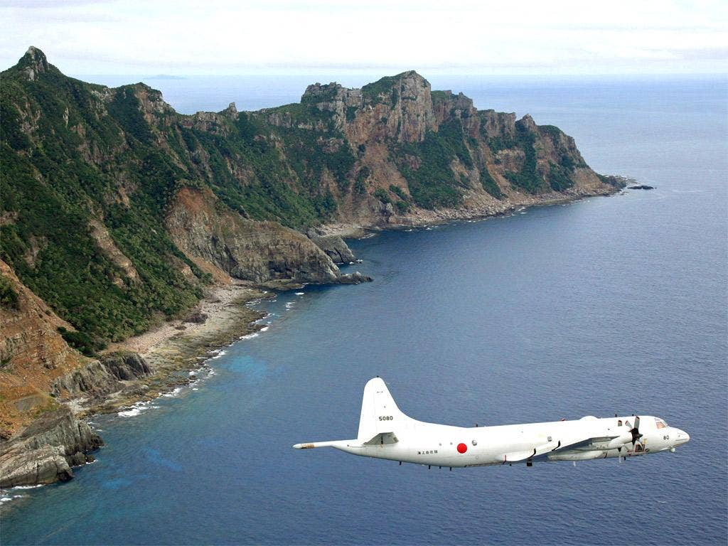 A Japanese surveillance plane flies over the disputed islands in the East China Sea, called the Senkaku in Japan and Diaoyu in China