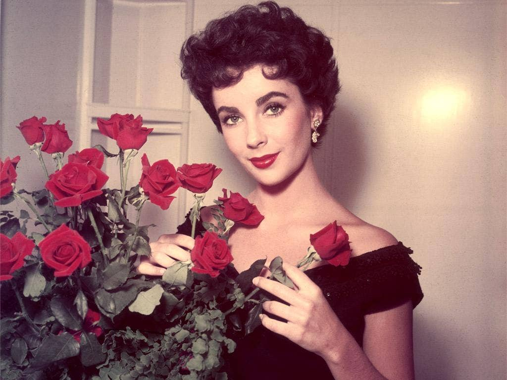 Strike a posy: Liz Taylor with first-night flowers