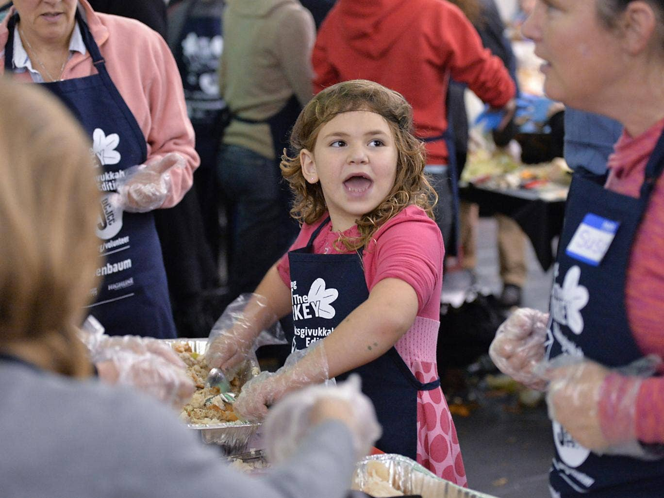 People prepare Thanksgiving meals for those in need at the District of Columbia Jewish Community Center in Washington as America prepares to celebrate Thanksgiving in its rare overlap with the Jewish holiday of Hanukkah, prompting the center to dub it 'Th