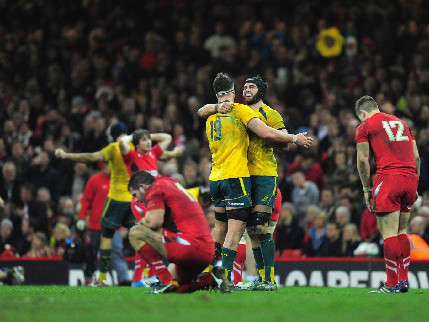 A disconsolate Wales team can't bare to look as Australia celebrate their win at the Millennium Stadium