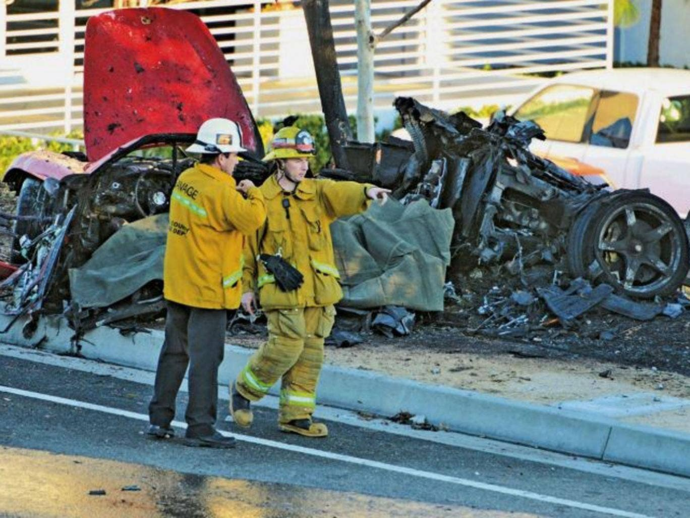 Sheriff's deputies work near the wreckage of a Porsche that crashed into a light pole on Hercules Street near Kelly Johnson Parkway in Valencia, California, north of Los Angeles
