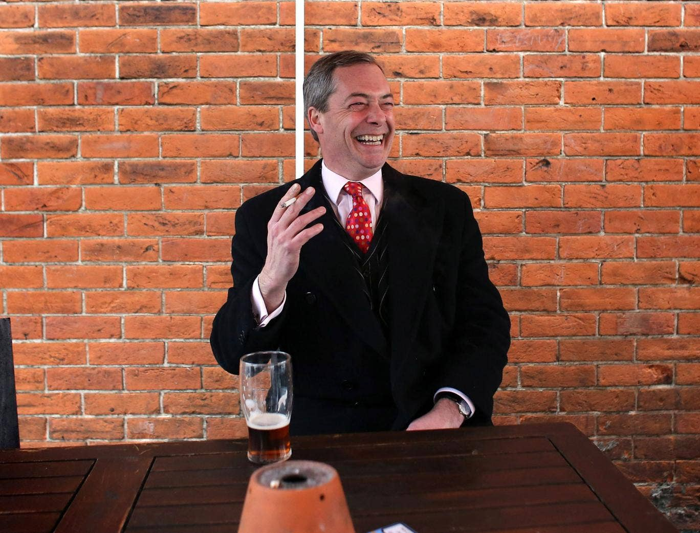 Nigel Farage smokes a cigarette and drinks a pint of beer as he takes a break in a pub during the by-election campaign for Eastleigh, Hampshire