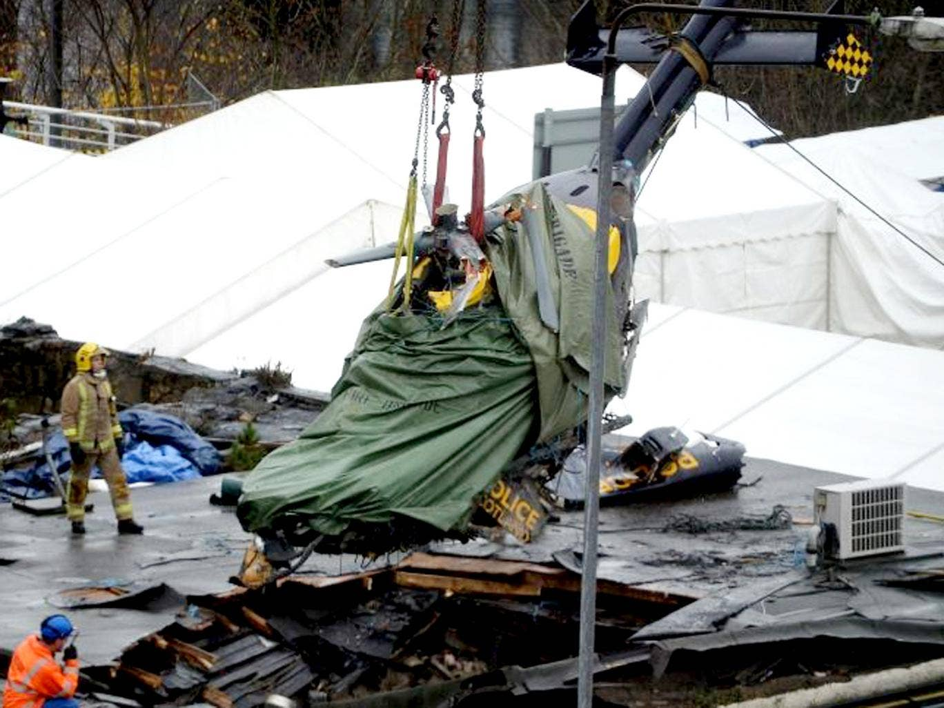 Rescuers lift the police helicopter wreckage from the roof of the The Clutha Pub in Glasgow, Scotland