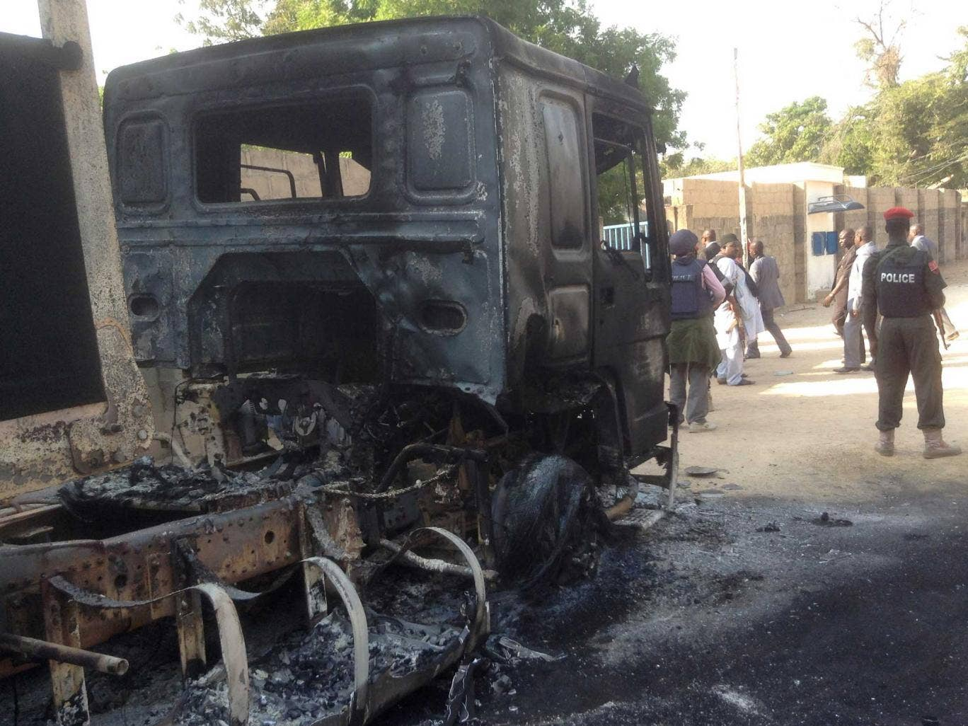 Policemen stand guard at a burnt-out truck following the attack