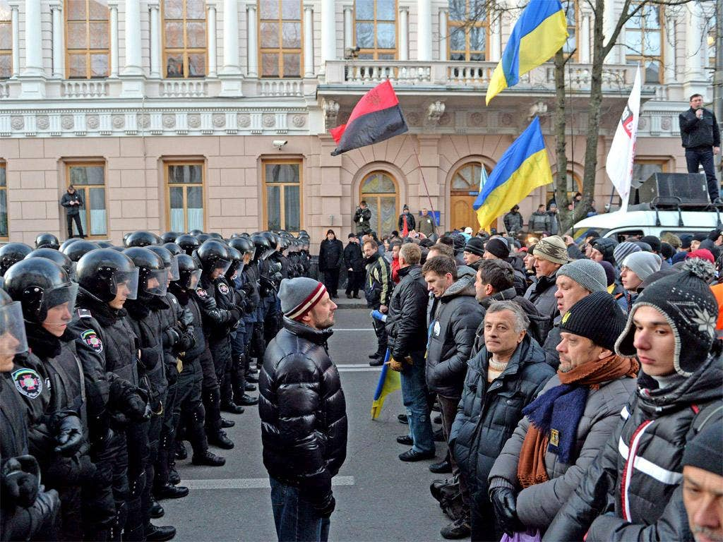 Protesters stand in front of riot policemen guarding the Ukrainian parliament in Kiev