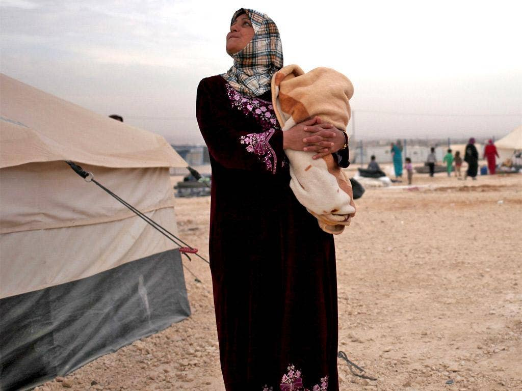A Syrian mother holds her child at a refugee camp, near the Syrian border, in Mafraq, Jordan