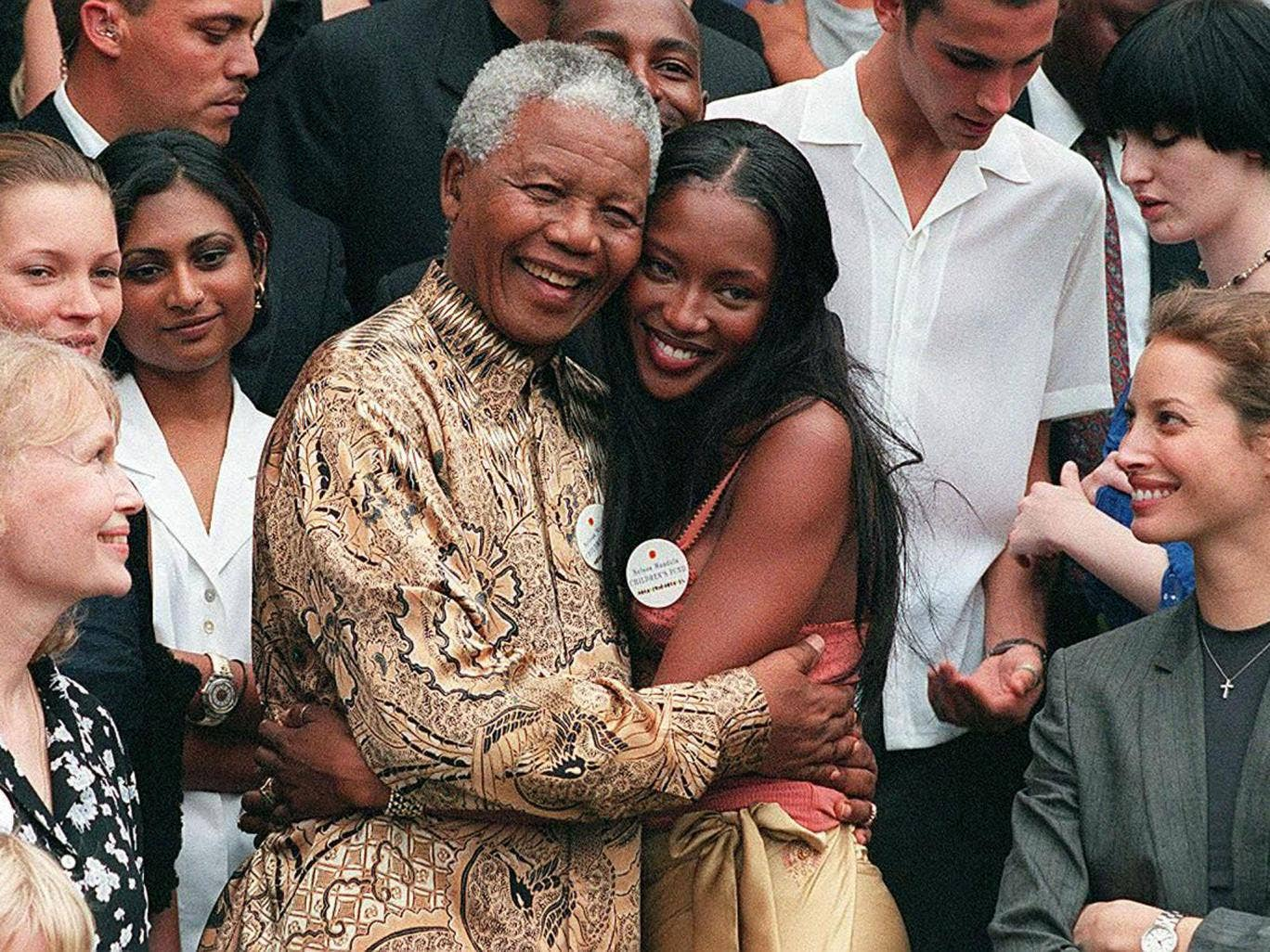 February 1998: Nelson Mandela (L) hugs British supermodel Naomi Campbell in front of American actress Mia Farrow, British model Kate Moss (second from left) and model Christy Turlington