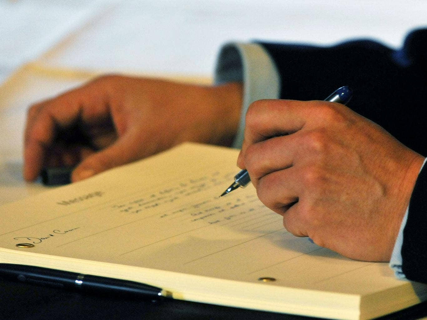 Britain's Prime Minister David Cameron signs the book of condolence at the South African Embassy in central London