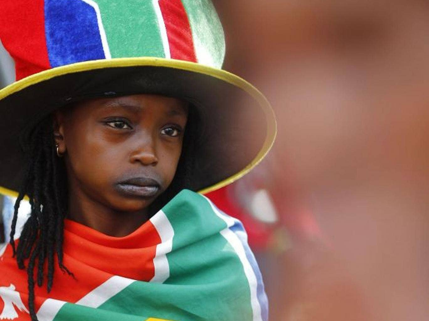 Tributes: A child in patriotic garb outside Mandela's former home in Soweto