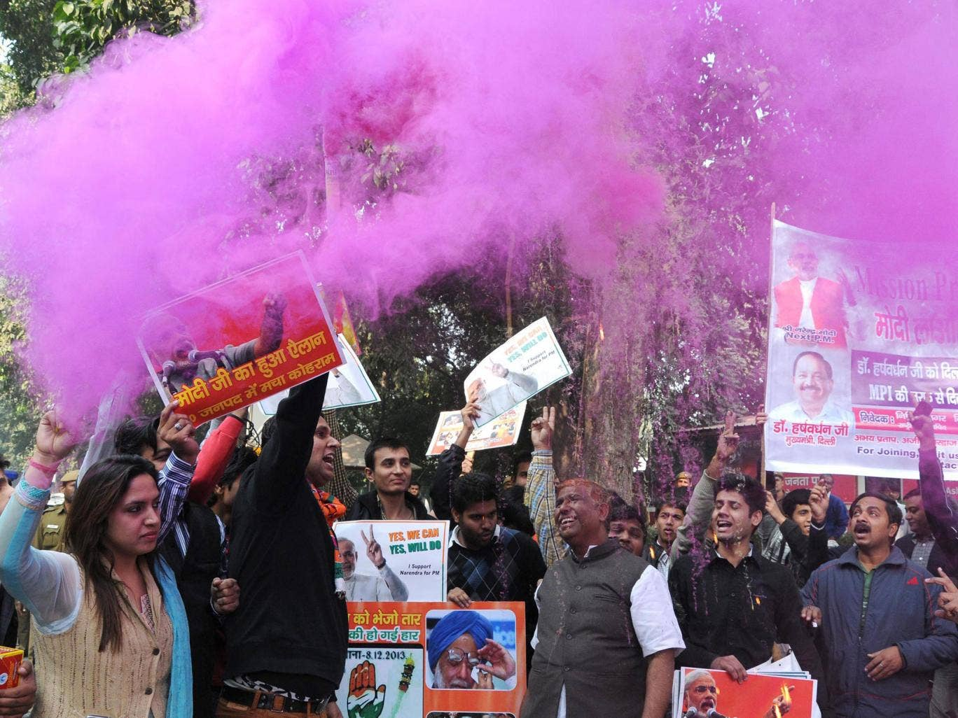 Supporters of the Indian Bharatiya Janata Party (BJP) spray color dust as they celebrate outside their party headquarter after the announcement of the results of the Assembly elections