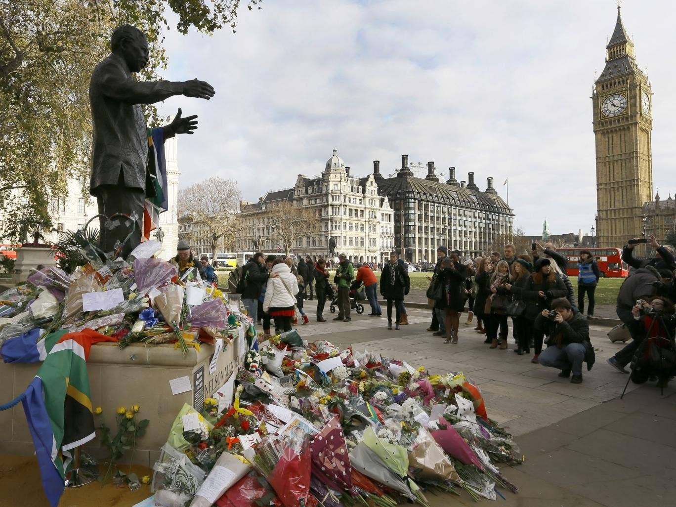 People gather to look at flowers and tributes left at the statue of Nelson Mandela in Parliament Square, London