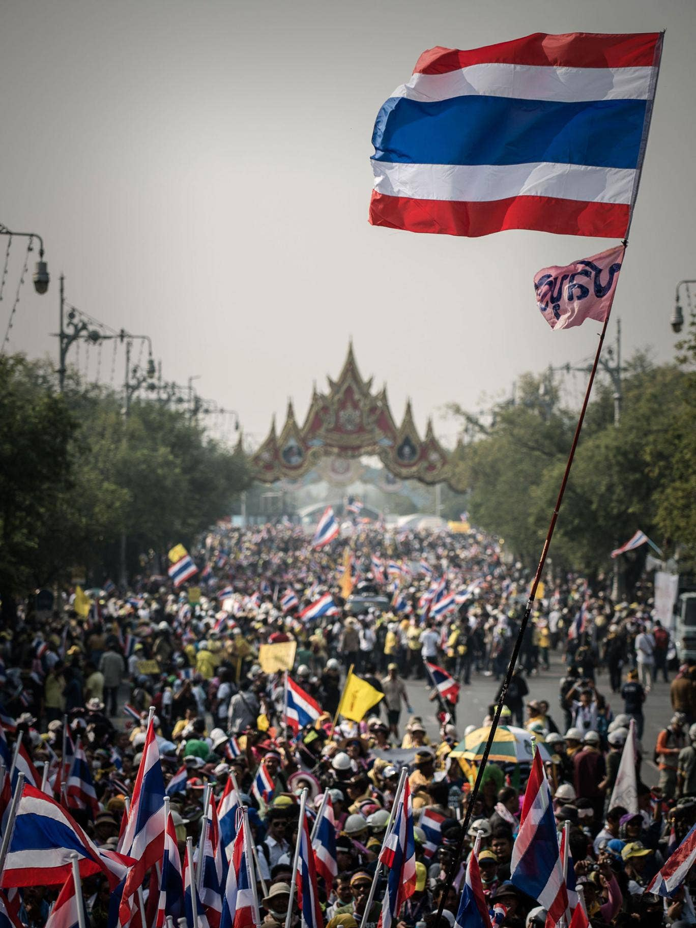 Demonstrators marching towards Government House in Bangkok; an estimated 100,000 protesters flooded the streets