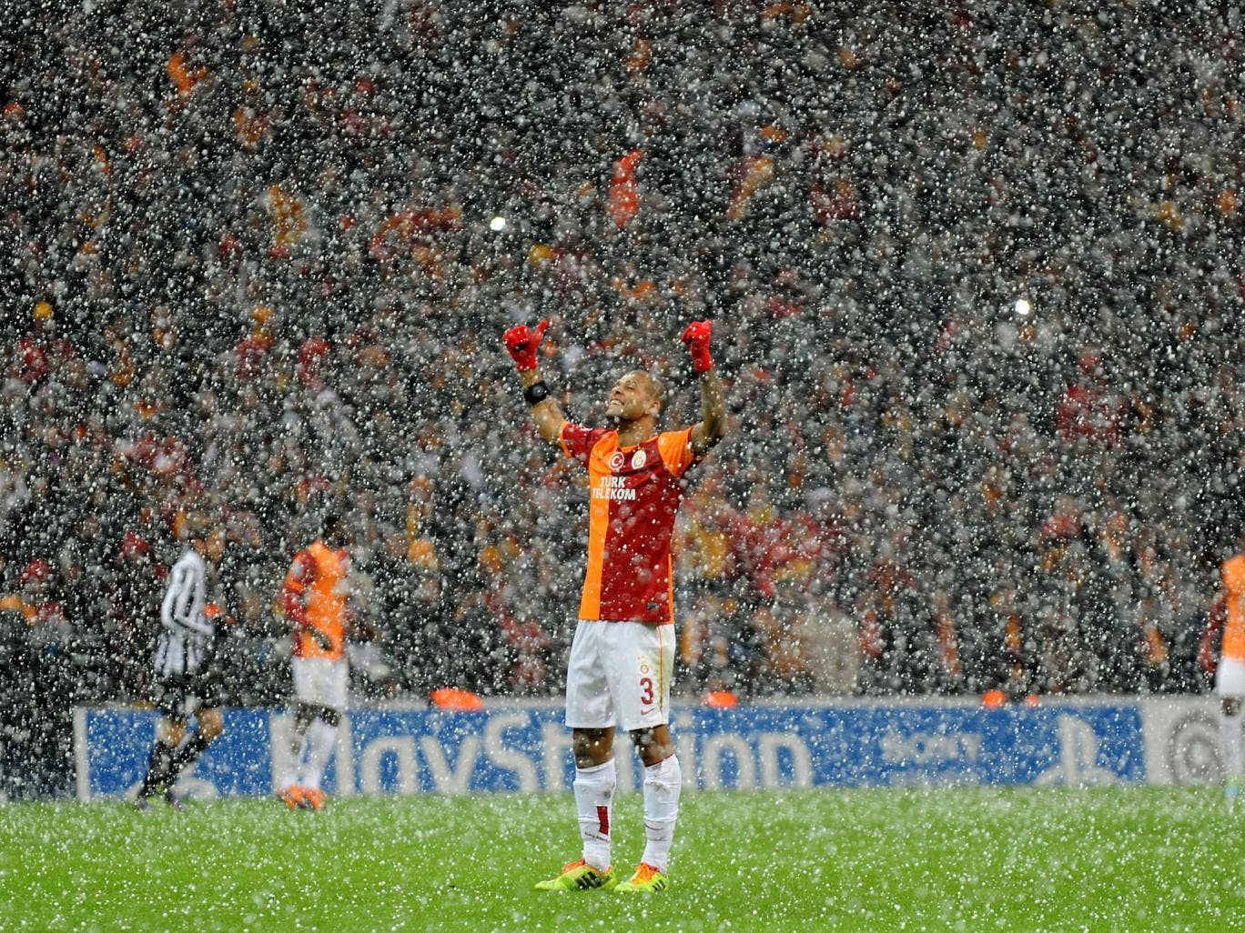 Galatasaray midfielder Felipe Melo raises his arms as the snow falls in Istanbul