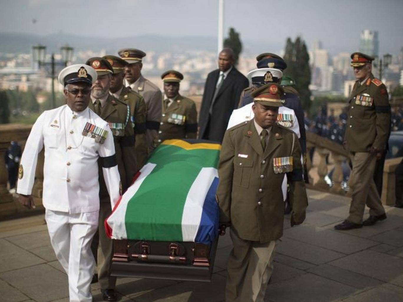 Military officers carry the coffin of South African former president Nelson Mandela to the Union Buildings marking the start of a three-day lying in state in Pretoria