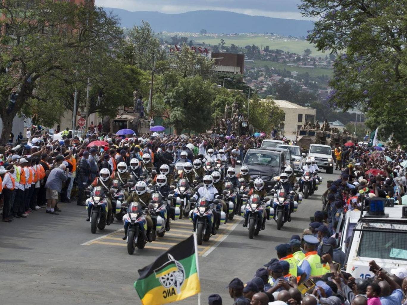 The motorcade transporting the body of Nelson Mandela, in black hearse, passes through crowds of mourners gathered in the town of Mthatha on its way to Qunu