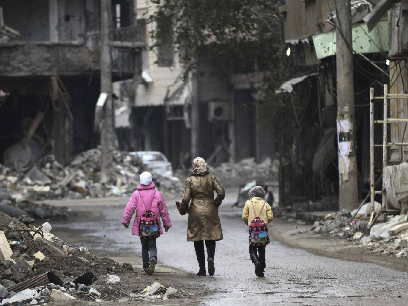 A woman walks with her children along a damaged street filled with debris in Deir al-Zor, eastern Syria