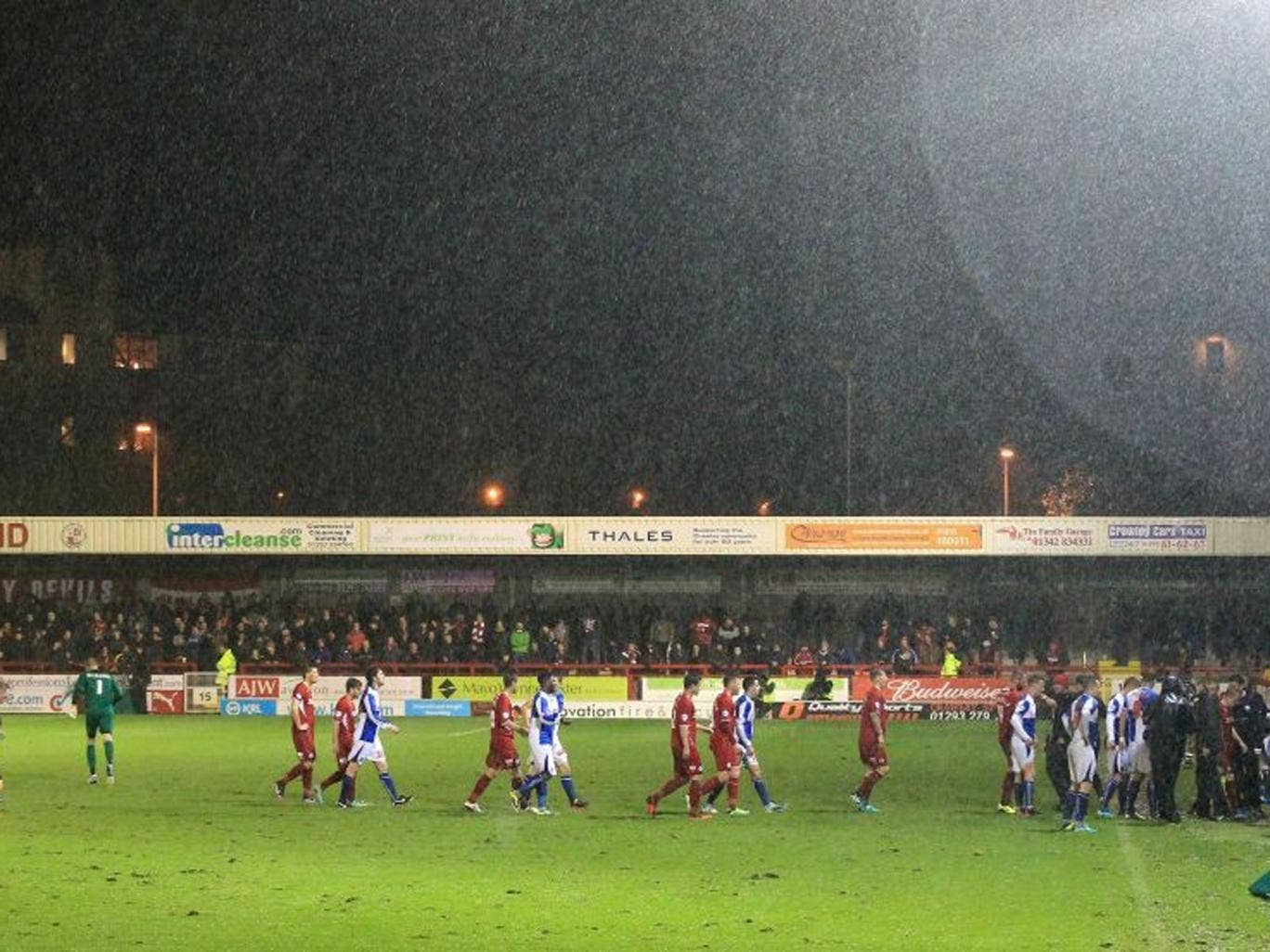 Crawley Town and Bristol Rovers players leave the pitch as the match is abandoned due to bad weather